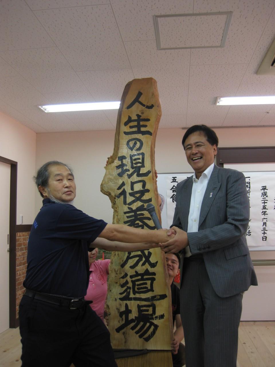 銘板を自筆した保坂世田谷区長と事業者の藤原理事長